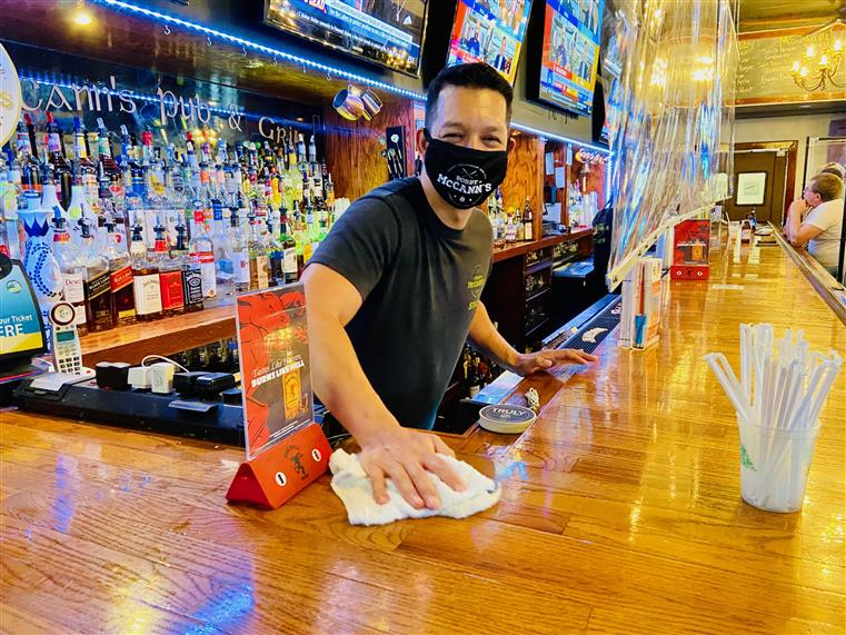 bartender wearing a mask and cleaning the bar