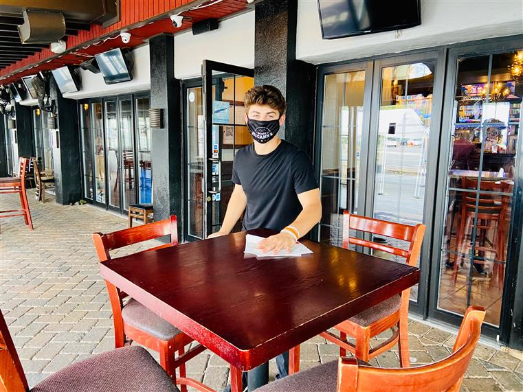 server wearing a mask and cleaning a table