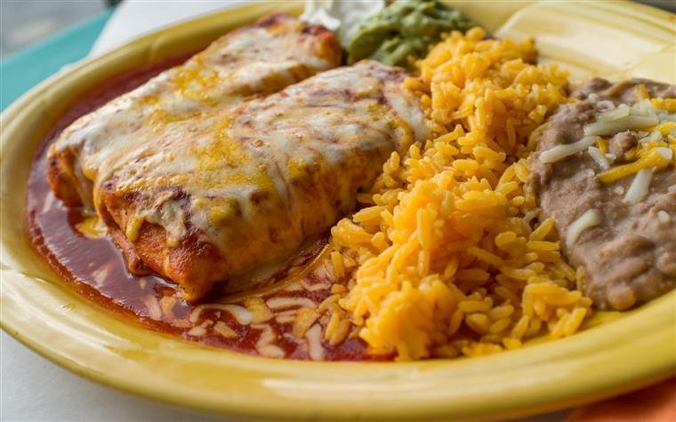 two chimichangas in spicy sauce with cheese. rice and beans on the side.