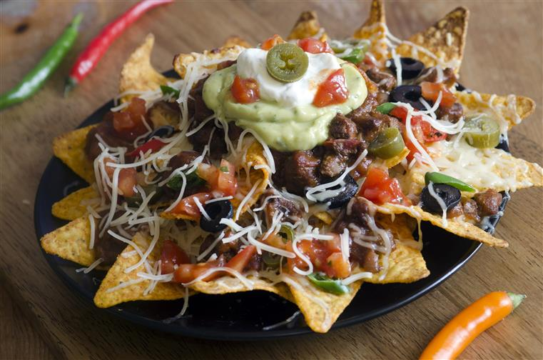 nachos loaded with beef, salsa, cheese, guacamole, and jalapenos