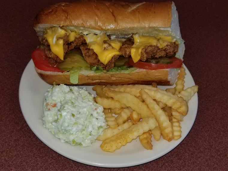 alligator po boy with cheese, pickles, tomato and lettuce on a plate with crinkle cut fries and cole slaw