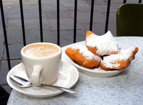cup of coffee and plate beignets topped with powdered sugar