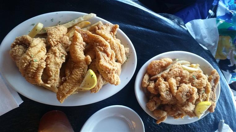 plates of fried shrimp, fried chcicken tenders, fried fish, and french fries