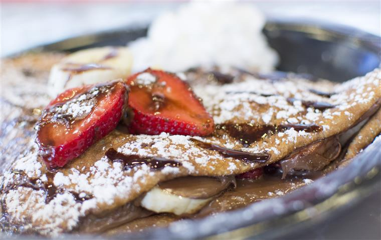 nutella crepe with banana slices, strawberry slices, chocolate sauce, and powdered sugar
