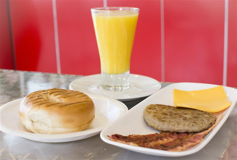 breakfast platter with a plain bagel, bacon strips. sausage patty, and slice of american cheese. glass of orange juice