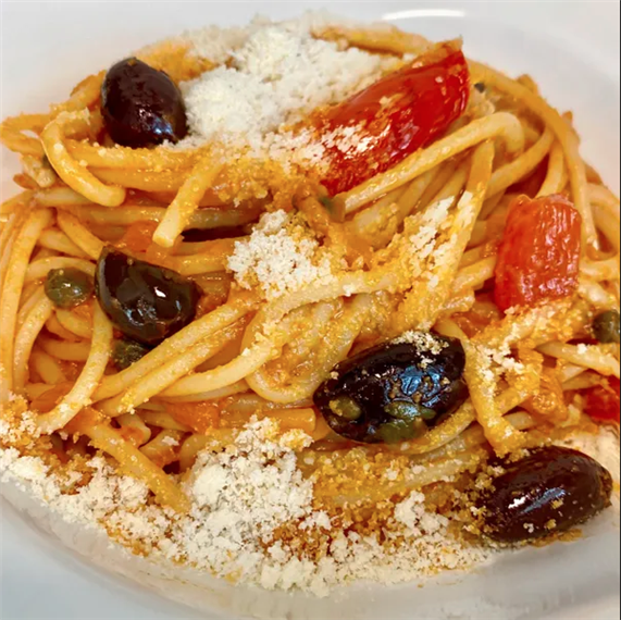 spaghetti pasta in a tomato sauce with olives and cheese