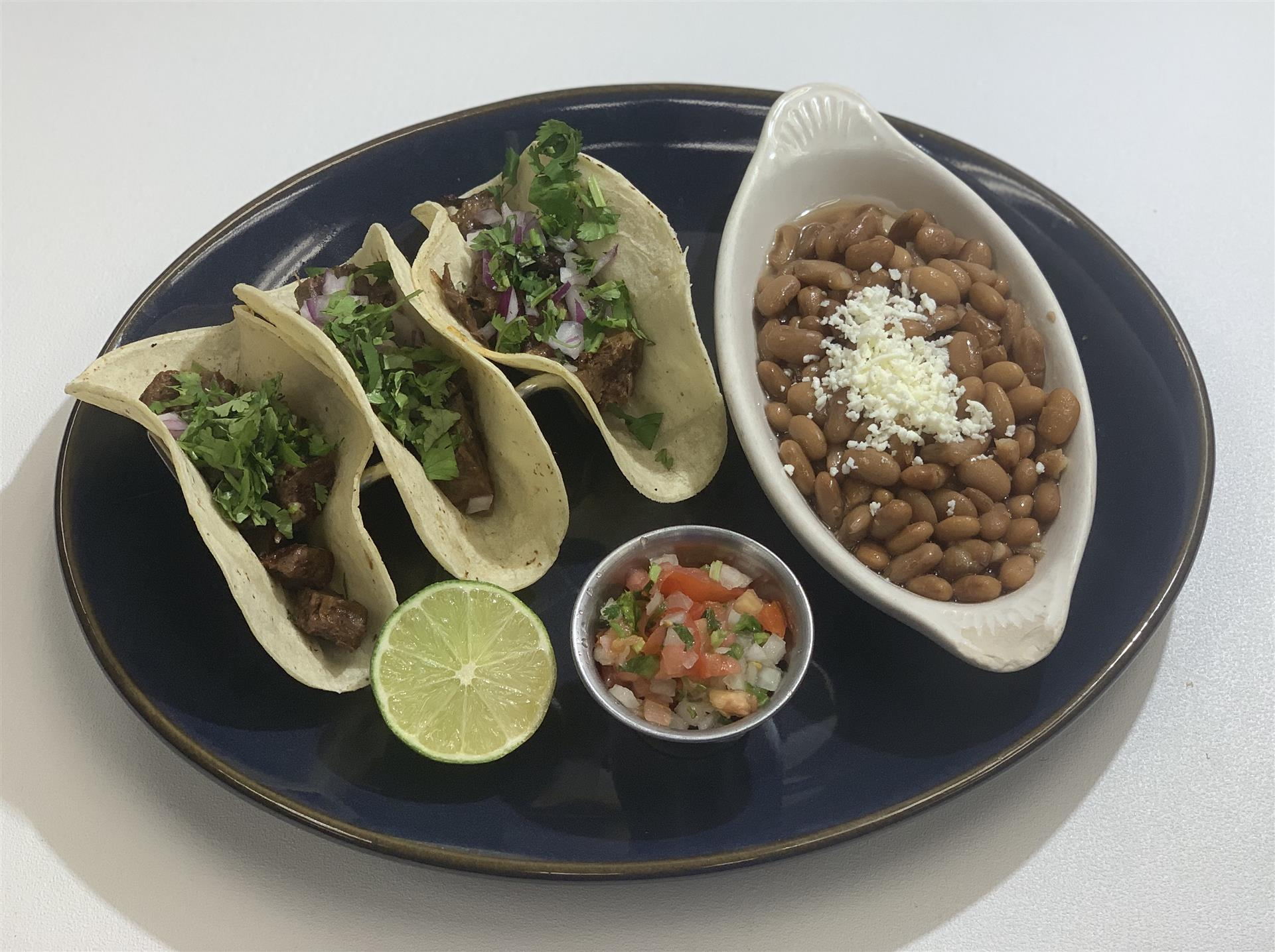 Three carne asada tacos served with whole beans, pico de gallo, chopped onions, cilantro, lime, and hot sauce