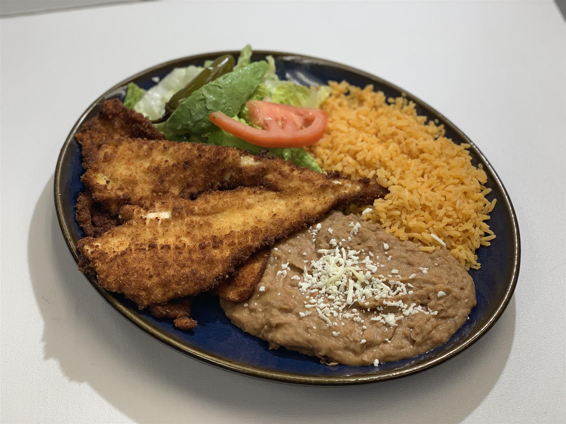 Guilotas: Fried whole quail with roasted tomatillo sauce, rice and beans.