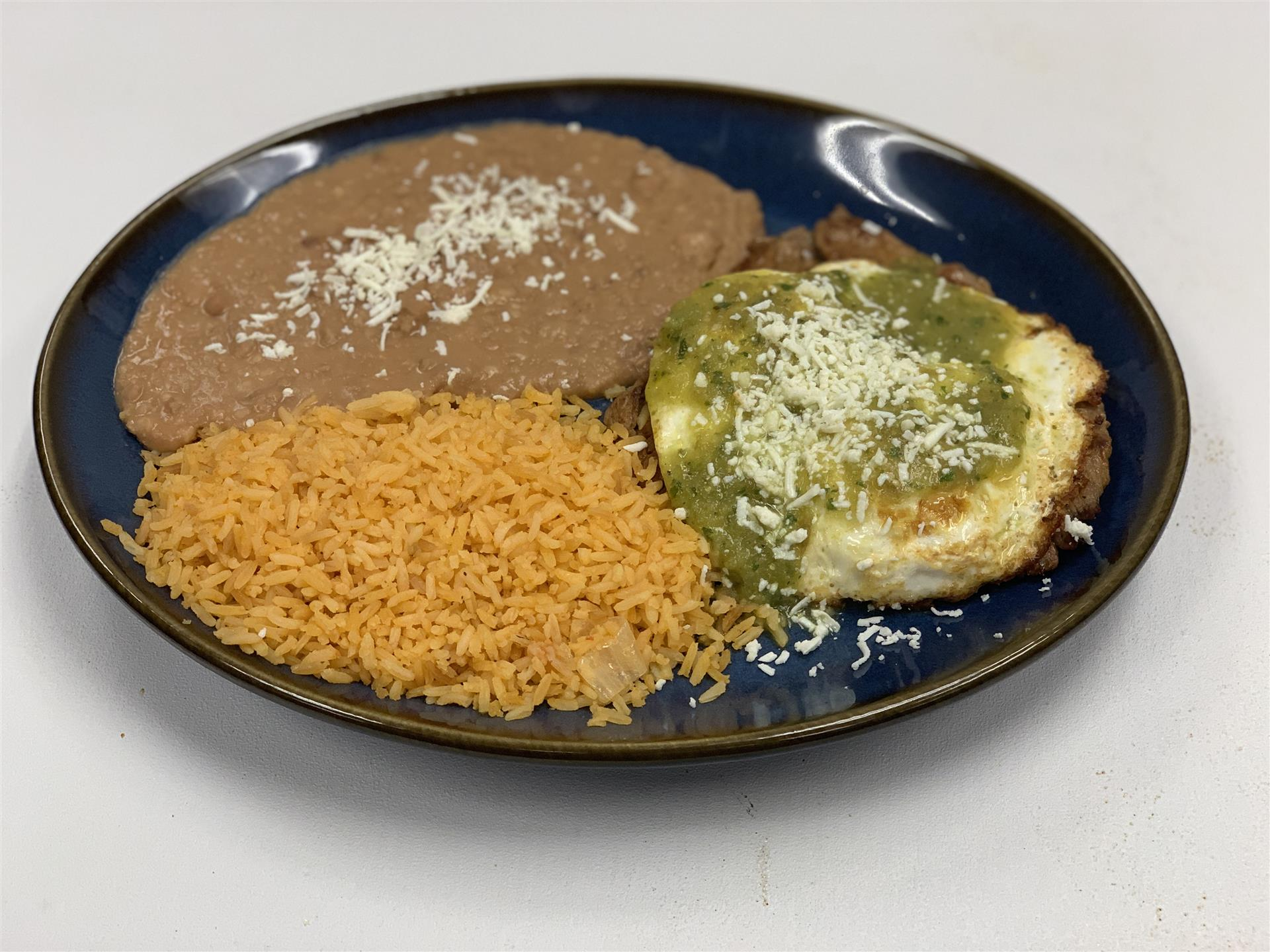 Huevos Azteca: Two eggs over easy, topped with cheese and green tomatillo sauce with carne asada, served with rice and beans