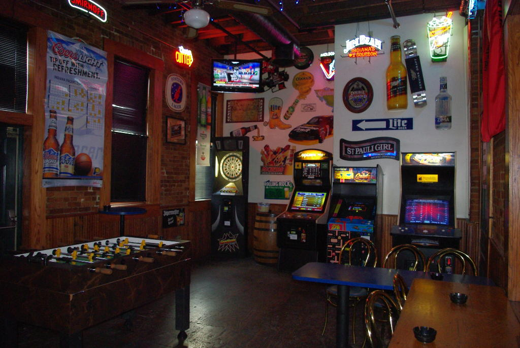 the game room with a TV, a foosball table, arcade games, and tables