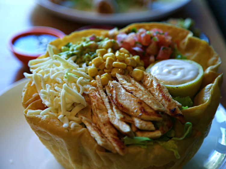 A taco salad in a hard shell bowl with chicken, corn, cheese tomato and guac