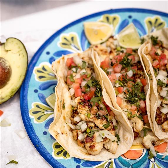 3 chicken tacos topped with tomato, cilantro and diced onion