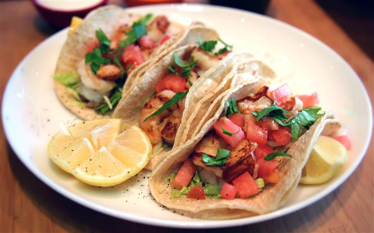 Shrimp tacos on a plate topped with cilantro, tomato, and lettuce