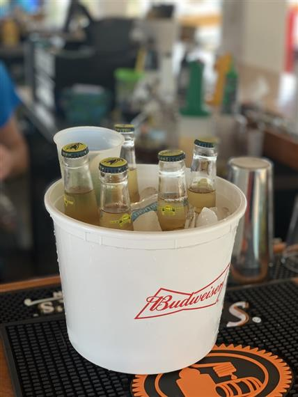 bucket of five beer bottles and cups