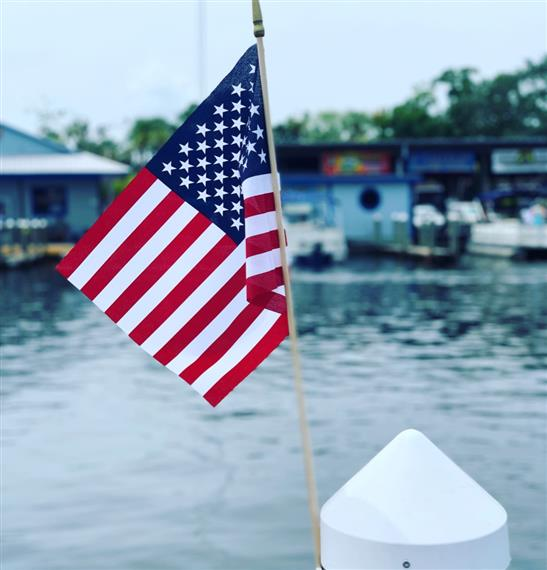 american flag on the dock in front of the water