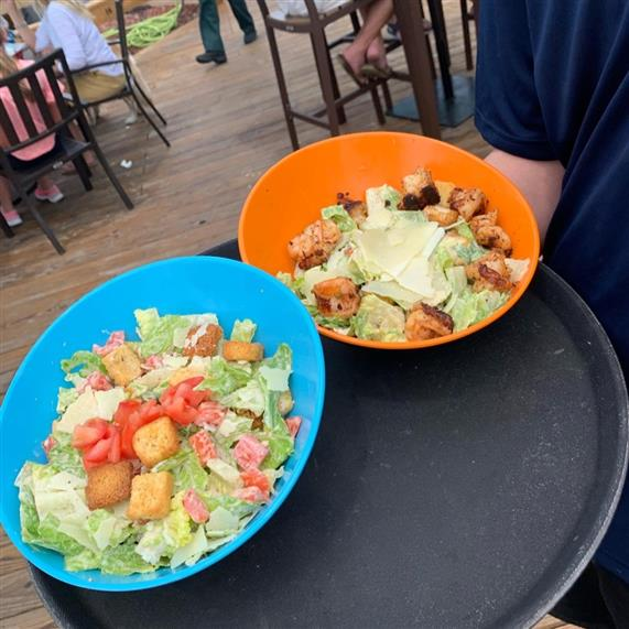 two salads on a serving tray being held by a waiter