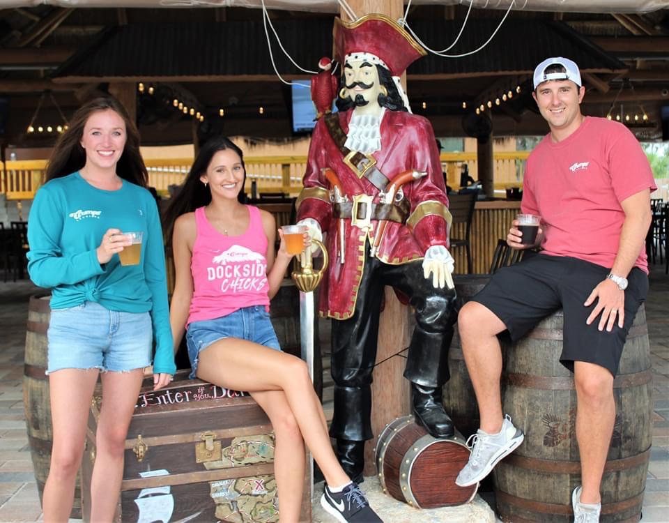 two women and a man posing with cocktails in front of a pirate statue