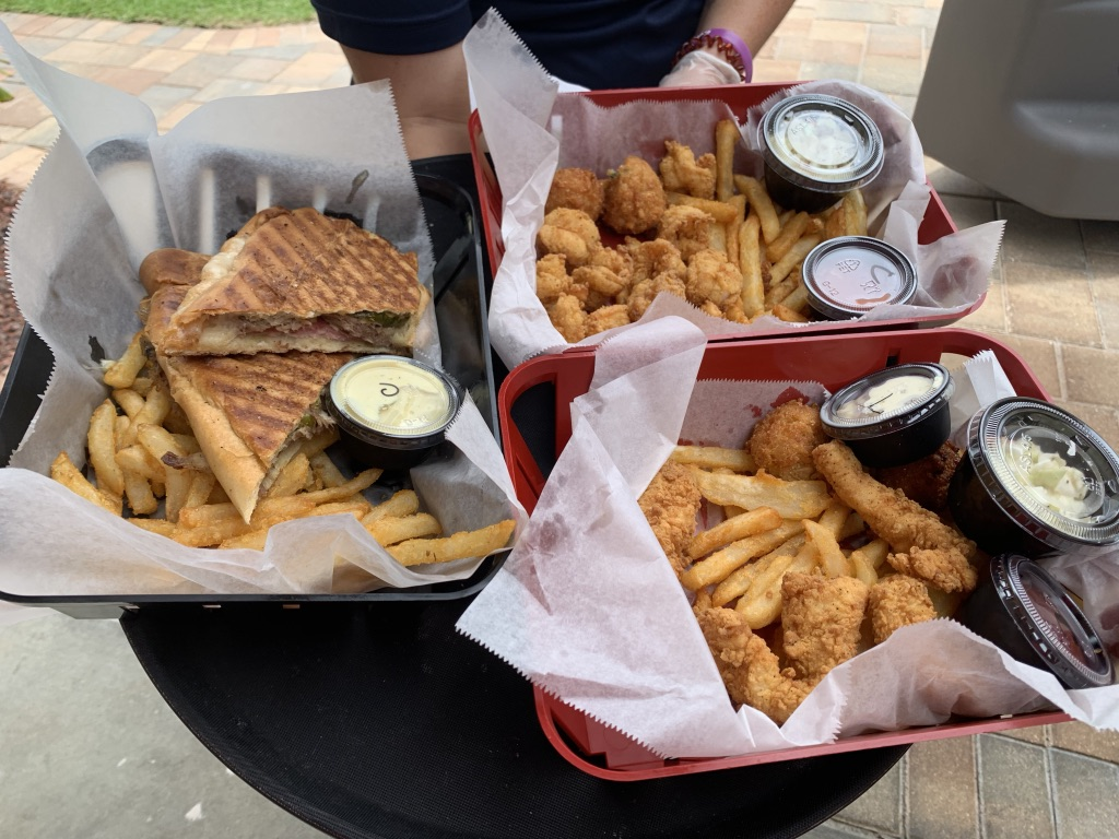 platters of chicken tenders, french fries, panini, and popcorn shrimp