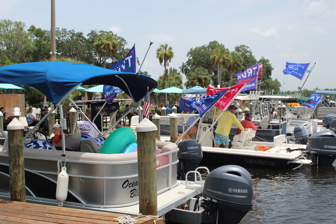 pontoon boats docked at the deck with Trump flags
