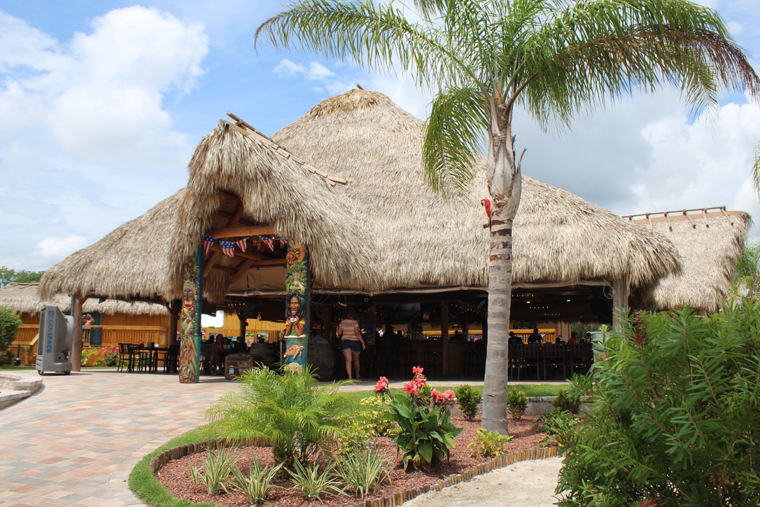 view of crumps with a straw roof and palm trees