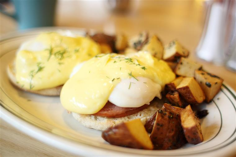 eggs benedict on a plate with a side of breakfast potatoes