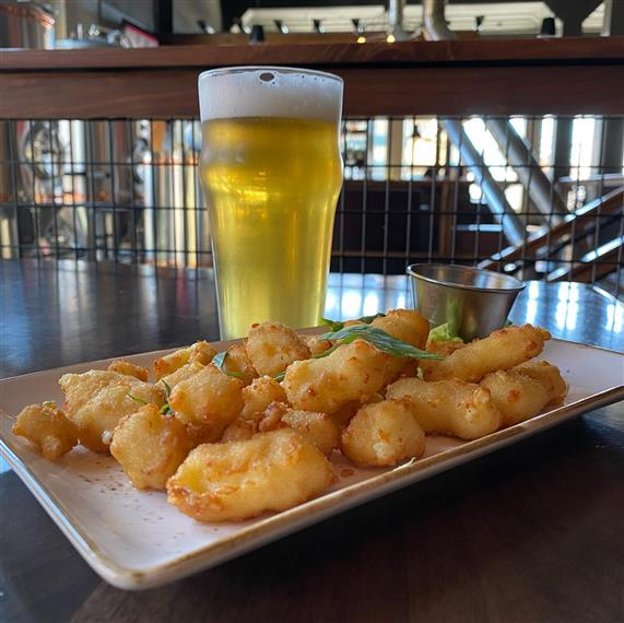 glass of beer with a plate of cheese curds