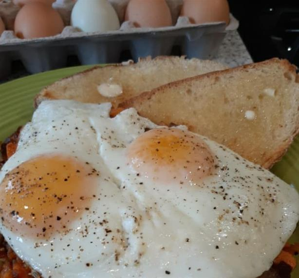 fresh sunny side up eggs with buttered toast on the side