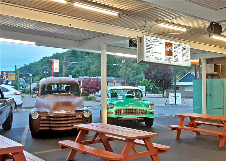 Our outdoor seating area with picnic benches and vintage cars parked outside