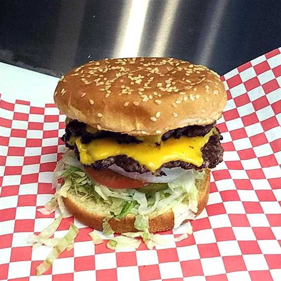 A double cheeseburger topped with onion, tomato, and lettuce