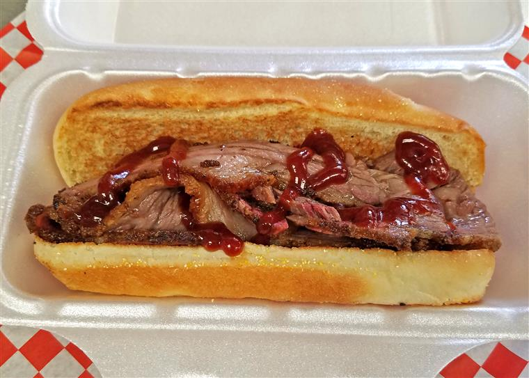 A roast beef sandwich topped with BBQ sauce