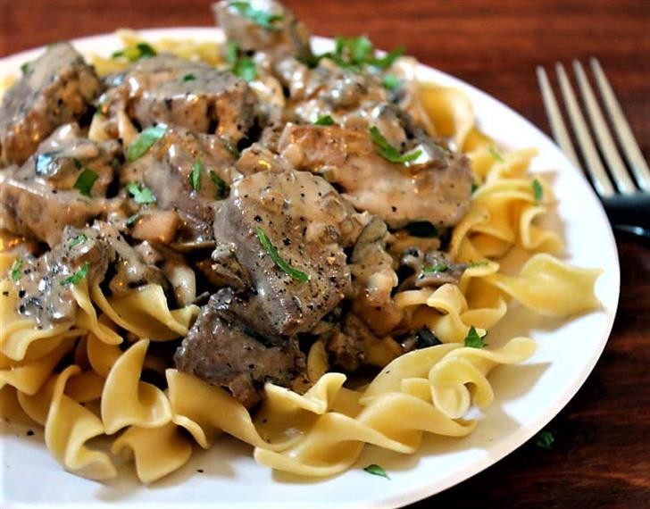 beef tidbits in a sauce on top of egg noodles