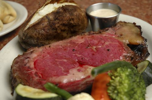 prime rib with vegetables and a baked potato