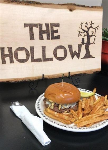 "cheeseburger, french fries, and a pickle spear on a plate in front of a wooden ""The Hollow"" sign"