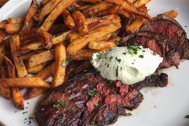 sliced steak with garlic butter and french fries