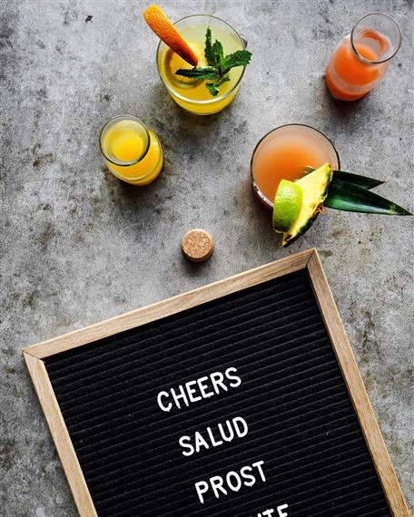 """assorted cocktails with a sign that says """"cheers. salud. prost"""""""