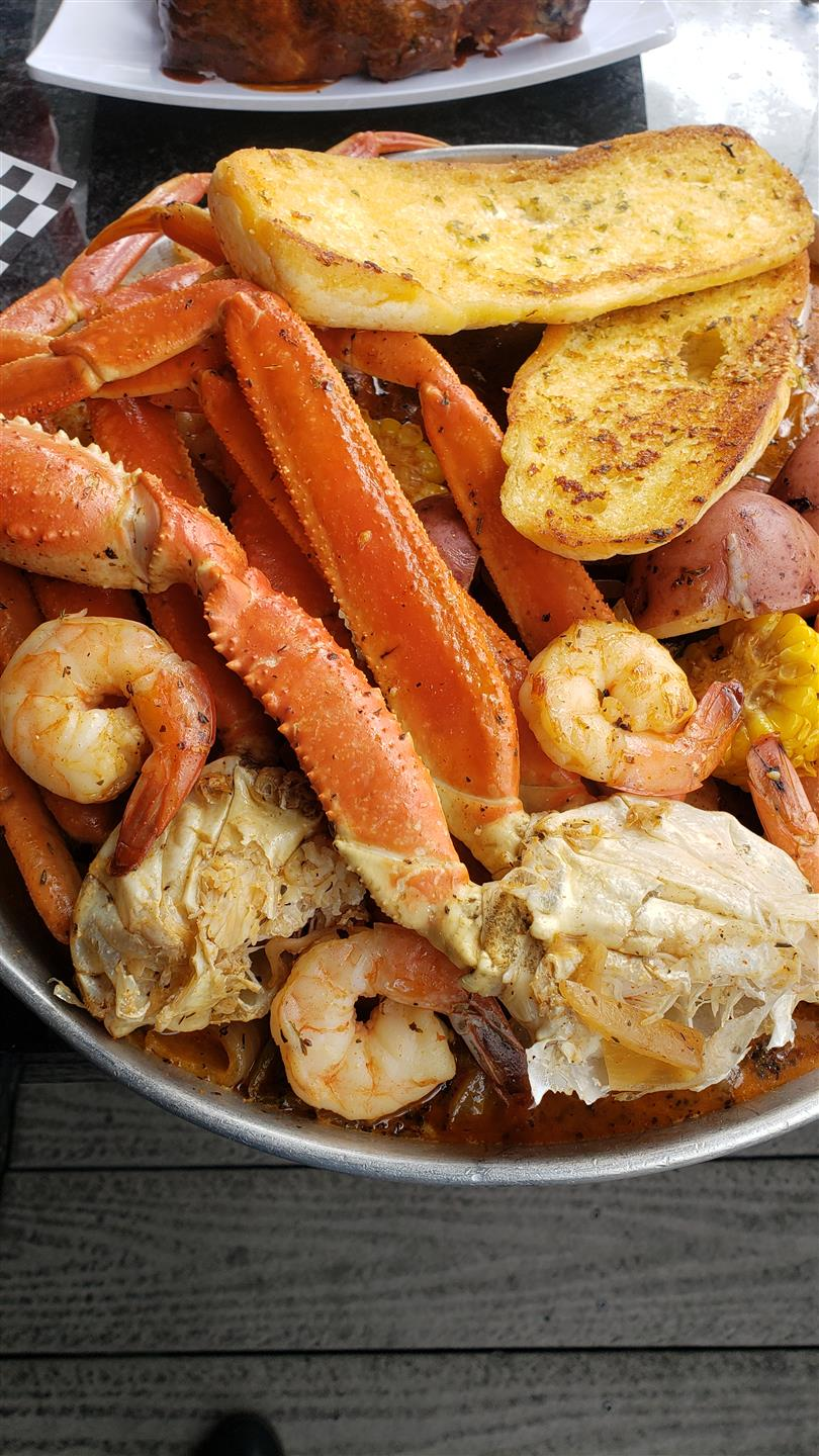 A bowl filled with seafood such as crab legs and shrimp
