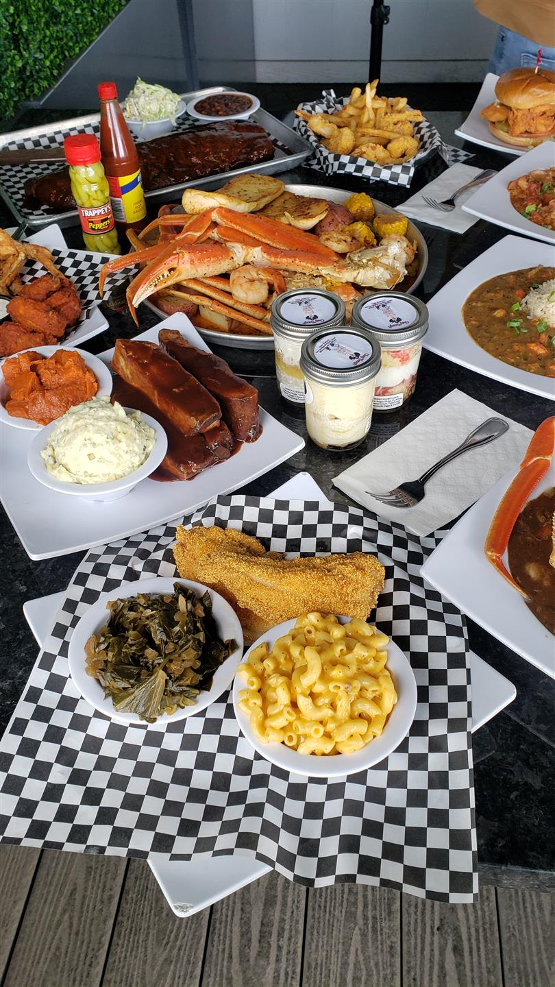 A table filled with multiple dishes such as ribs, a seafood bowl, wings, macaroni and cheese, fried chicken and green beans