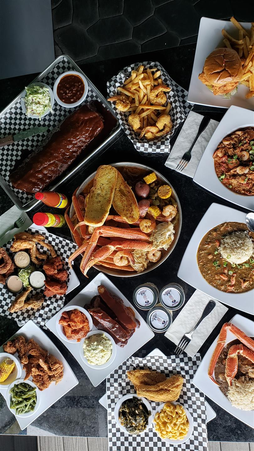 A table filled with multiple dishes such as ribs, a seafood bowl, wings and gumbo