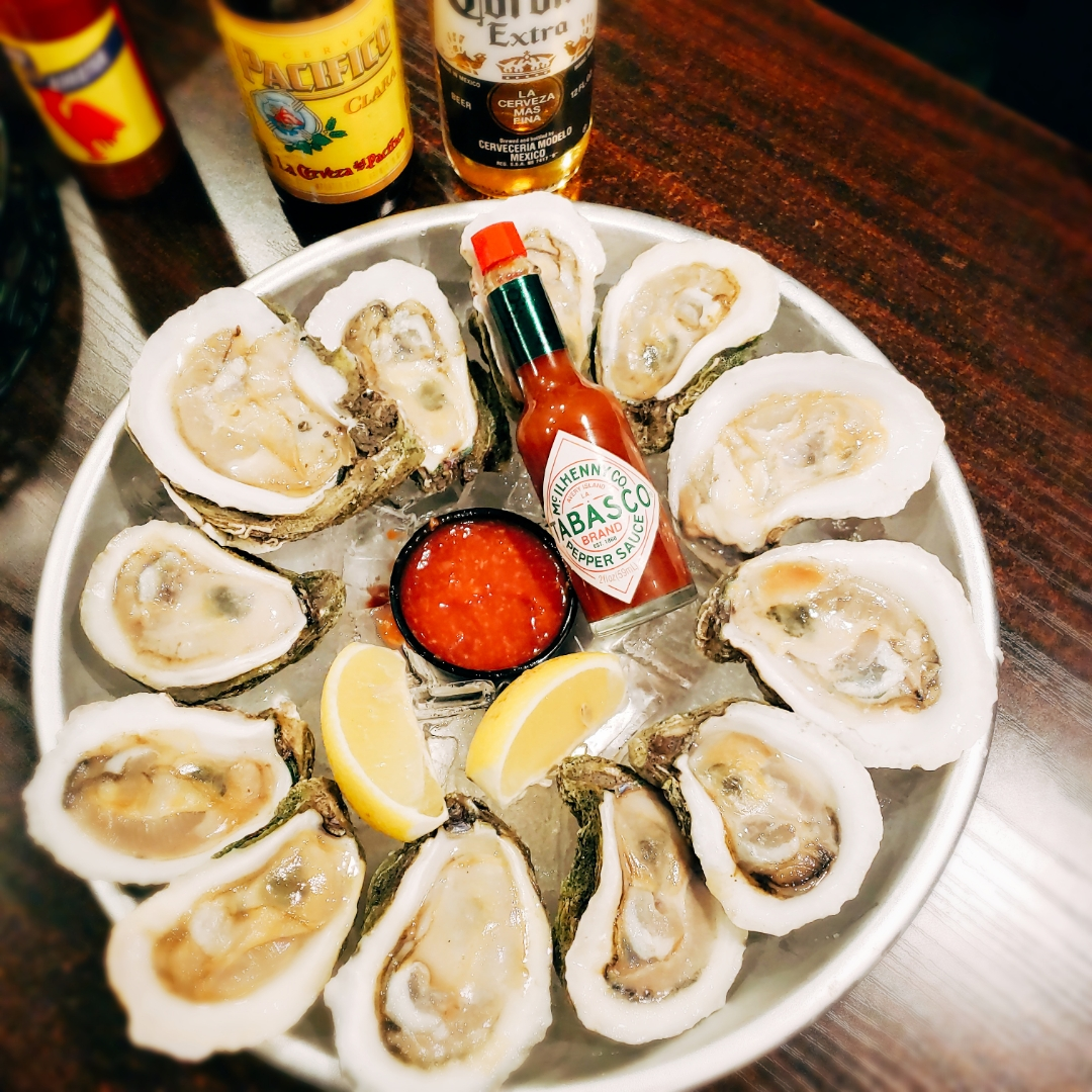 Oysters in a bowl over ice with hot sauce in the center
