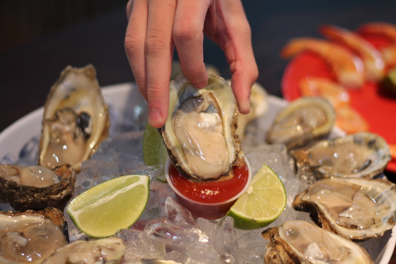 A hand dipping an oyster into sauce