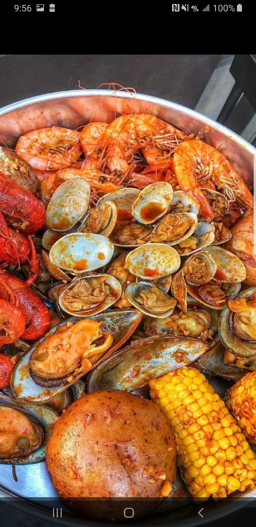 A bowl filled with various seafood options such as crawfish, crab legs, clams, shrimp and lobster