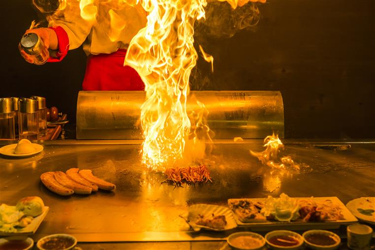 hibachi grill with flame and meats on griddle