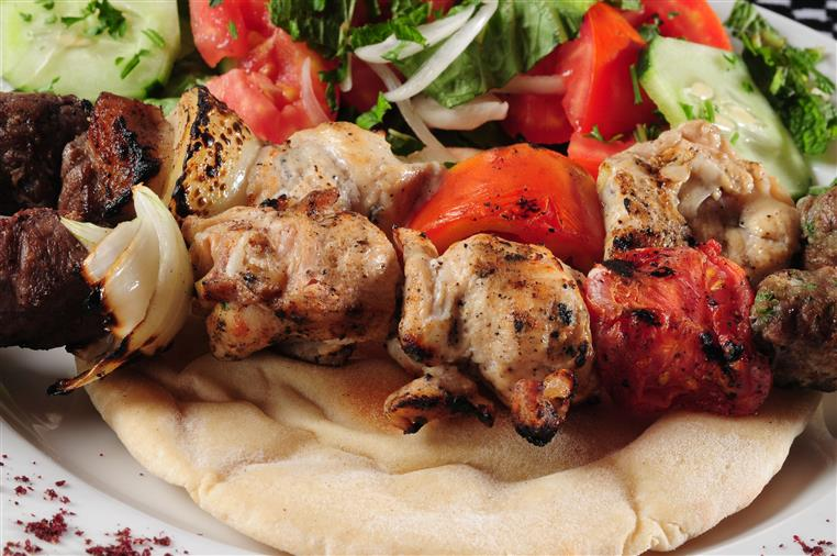 chicken kabobs over a pita with a side salad