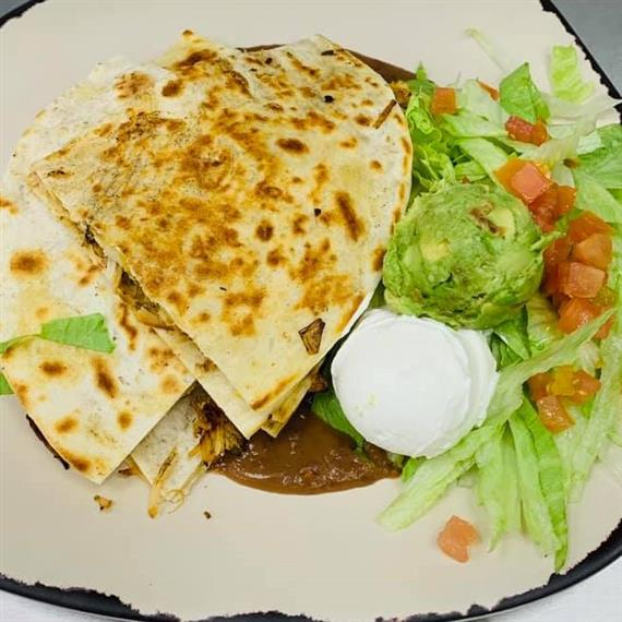 chicken quesadilla with guacamole, sour cream, lettuce and tomato