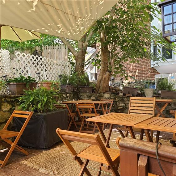 outdoor dining area with chairs, tables, and greenery