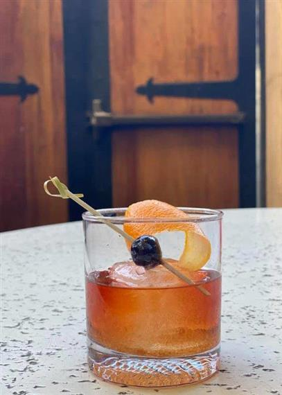 A cocktail on ice garnished with a blueberry and shaved orange