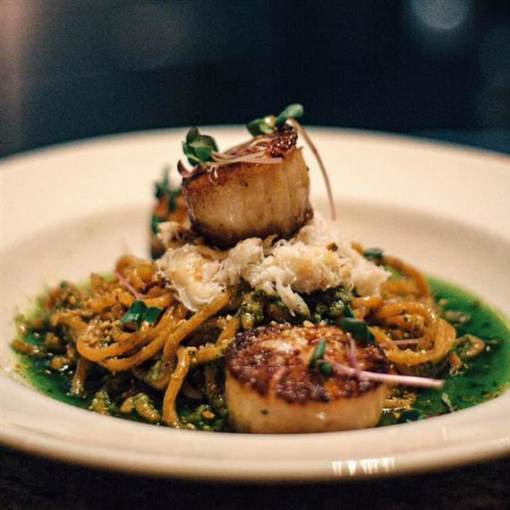 A quinoa and noodle salad topped with a cooked scallop