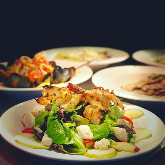 assorted italian dishes, including salad with shrimp and a seafood pasta