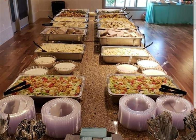 long table setup with assorted trays of food