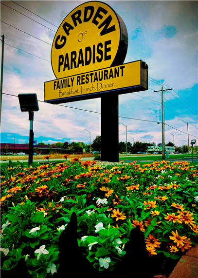 The Garden of Paradise outdoor sign surrounded by flowers